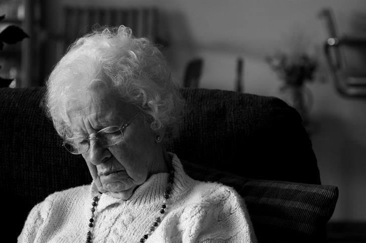 הקשר בין שינה לקויה לאיבוד שיווי משקל: אישה קשישה ישנה על כיסא
