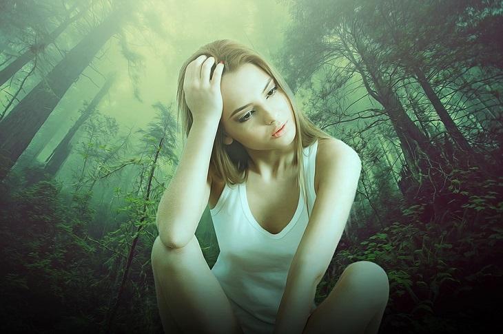 שאלות לקבל החלטות: אישה יושבת ומעבירה יד בשערה וברקע יער