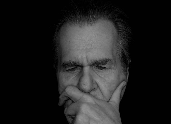 שאלות לקבל החלטות: גבר מבוגר מניח את ידו על פניו ותוהה