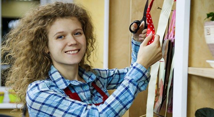 הרגלים לחוזק מנטלי: בחורה עומדת בחנות וחותכת סרט אדום עם מספריים