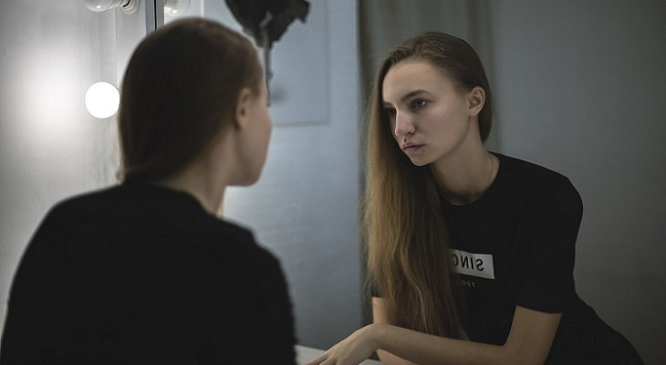 הרגלים לחוזק מנטלי: בחורה מביטה בהשתקפות שלה מול מראה