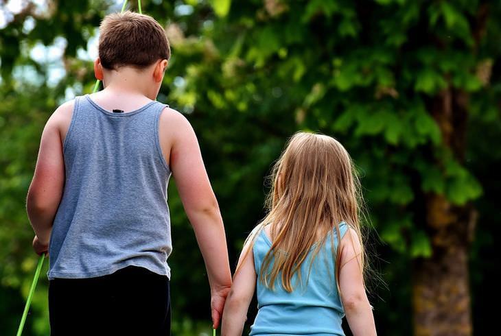 משפחות אומנה וקלט: ילד אוחז בידה של ילדה קטנה ממנו בזמן שהם צועדים בחוץ