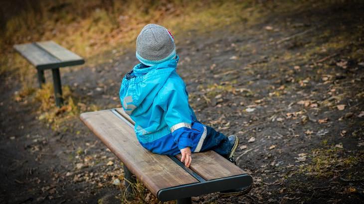 משפחות אומנה וקלט: ילד קטן יושב לבדו על ספסל בגינה
