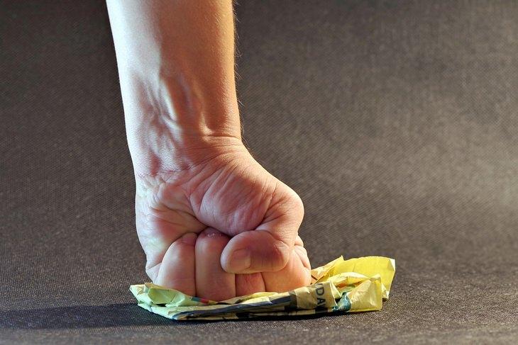 מיתוסים לגבי לחץ: יד מטיחה אגרוף בניירות על שולחן