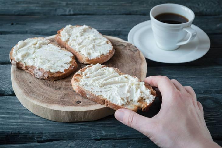 יד מחזיקה פרוסת לחם עם ריקוטה
