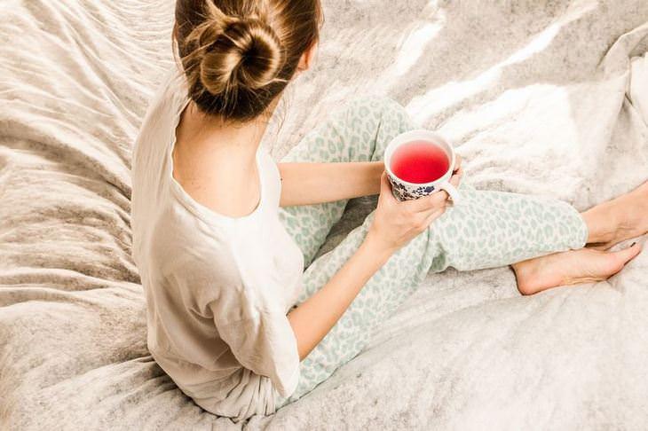 טיפים שיעזרו לכם להישאררגועים: אישה יושבת עם כוס תה במיטה