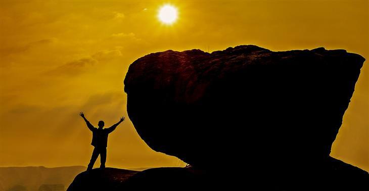 סימנים שאתם לא עושים את מה שאתם רוצים: איש עומד ליד סלע ענק ומרים את ידיו לאוויר
