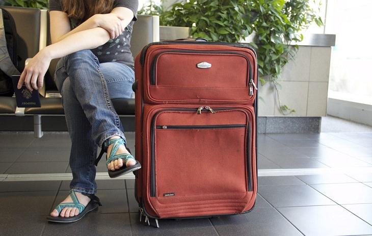 מדריך לטיסות לואו קוסט: אישה יושבת ליד מזוודה באולם נוסעים של שדה תעופה