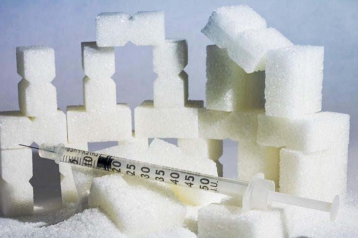 יתרונות בריאותיים של חרדל: מגדל קוביות סוכר ועליו מזרק