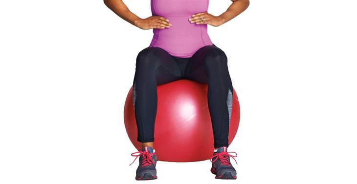 תרגילי כושר לאחר היריון: אישה יושבת על כדור פיזיו גדול