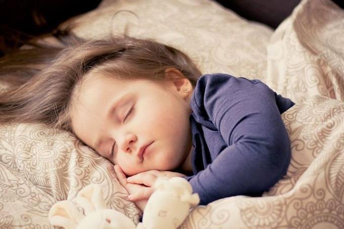 ילדה ישנה עם דובי