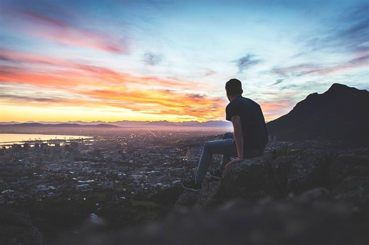 עקרונות לחיים טובים: איש יושב על הר ובוהה בעיר בשעת השקיעה