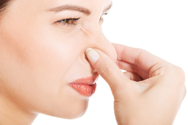 מזונות שמשפיעים על ריח הגוף: אשה סותמת את אפה עם אצבעותיה