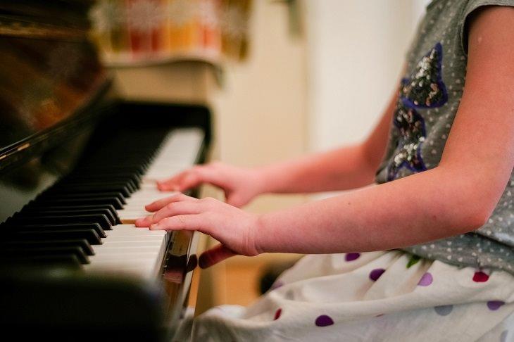 גורמים מוכחים מדעית לאינטליגנציה גבוהה: ילדה מנגנת בפסנתר