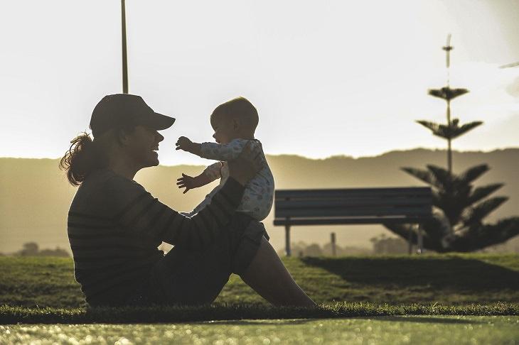 מחקרים עדכניים על הורות: אמא יושבת עם תינוקה על ברכיה ומחייכת אליו