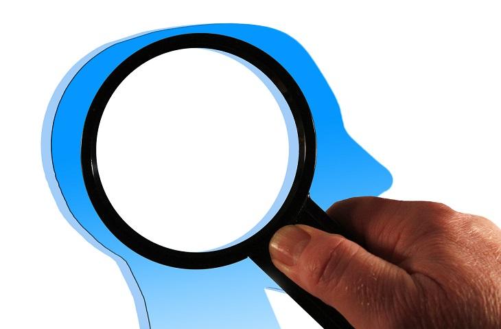גורמים מוכחים מדעית לאינטליגנציה גבוהה: איור של זכוכית מגדלת על גבי ראשו של אדם