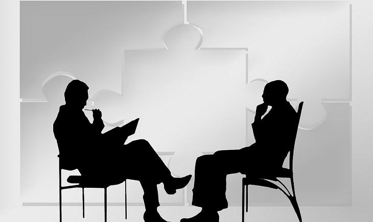 הטיות לוגיות שחשוב לזהות: צלליות של שני גברים מדברים מול שולחן