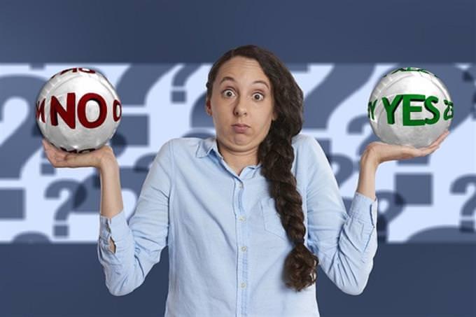 """אישה מתלבטת שבידיה כדורים עם המילים """"כן"""" ו""""לא"""" בתוכם"""
