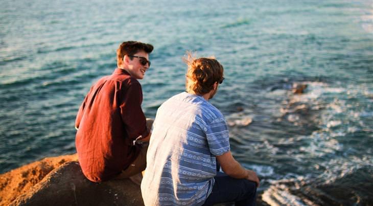 עצות לחיים מחולת סרטן בת 90: שני חברים יושבים על סלעים שמול הים