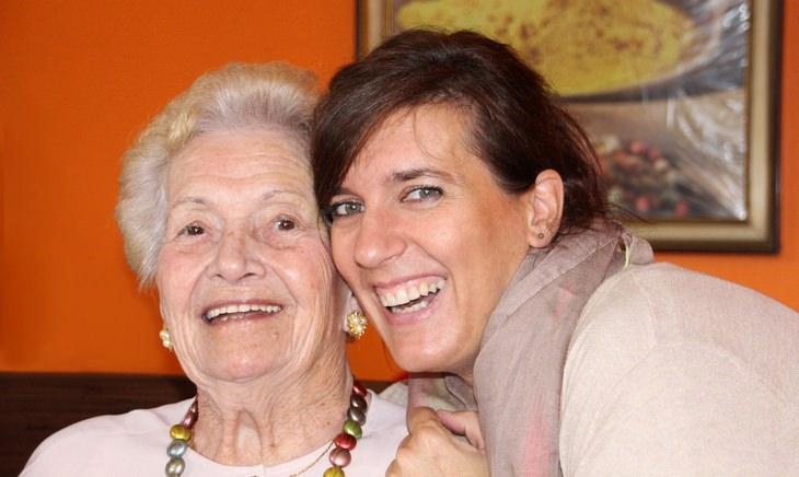 מחקר על הקשר בין בריאות וקשר משפחתי בגיל הזהב: אישה מבוגרת ואישה צעירה מתחבקות ומחייכות למצלמה