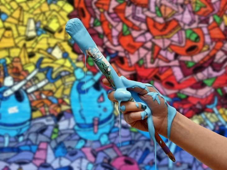 פעילויות של יום מעשים טובים: מברשת עם צבע על רקע קיר צבעוני
