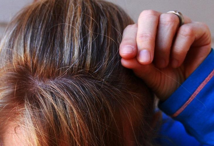 מאכלים שמזיקים לשיער: אישה תופסת בשערה לבנה בראשה