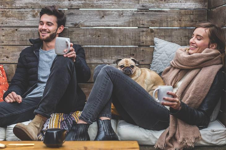 משברים נפוצים בחיי הנישואים: גבר ואישה יושבים אחד ליד השנייה עם כוסות משקה בידיהם וכלב ביניהם