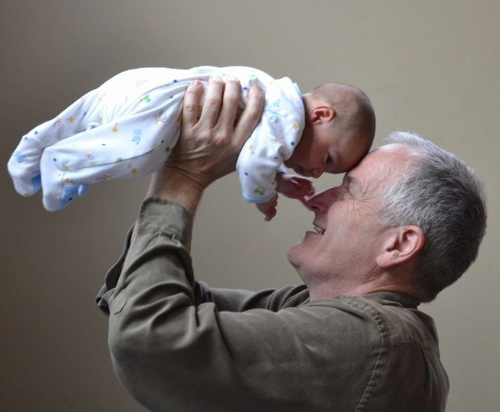ברכה לסבא וסבתא: סבא מחזיק את נכדו התינוק בידיו