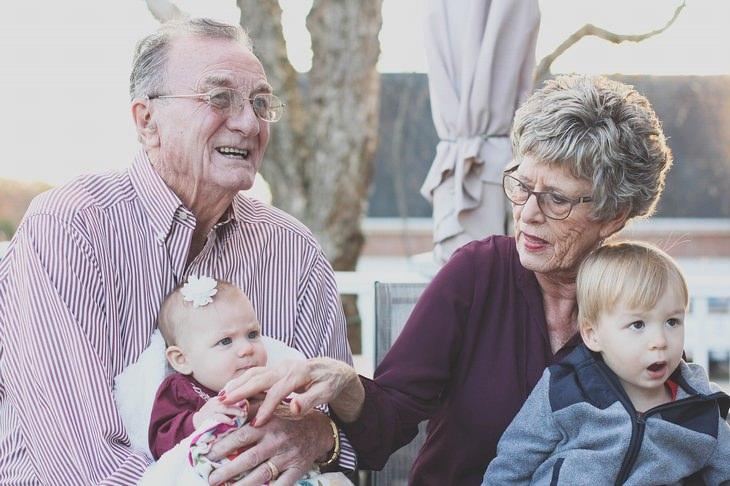 ברכה לסבא וסבתא: סבא וסבתא יושבים עם שני נכדים קטנים