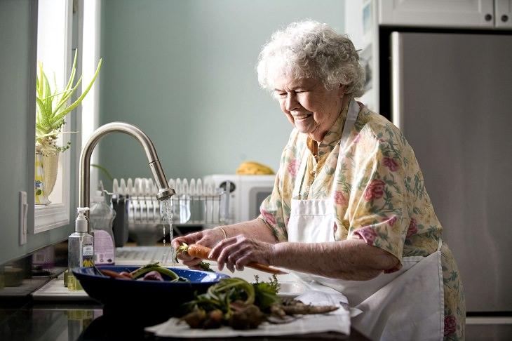 טיפים לבישול ואפייה: אשה מבוגרת בסינור עובדת במטבח