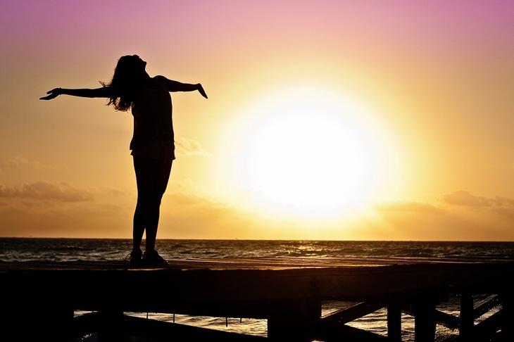 עצות רוחניות של פמה צ'ודרון: אישה עם זרועות פתוחות באור שקיעה