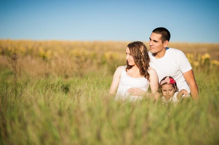 עצות לגידול ילדים מאושרים: אב אם ובת יושבים בשדה