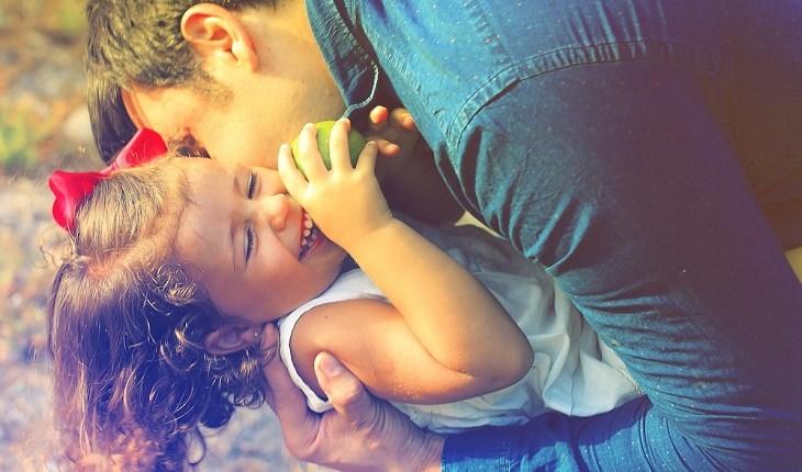 עצות לגידול ילדים מאושרים: אב מנשק את בתו הצוחקת
