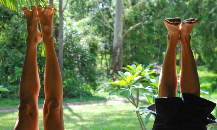 יתרונות בריאותיים של ביצוע עמידת ראש: רגליים באוויר של אנשים שמבצעים עמידת ראש