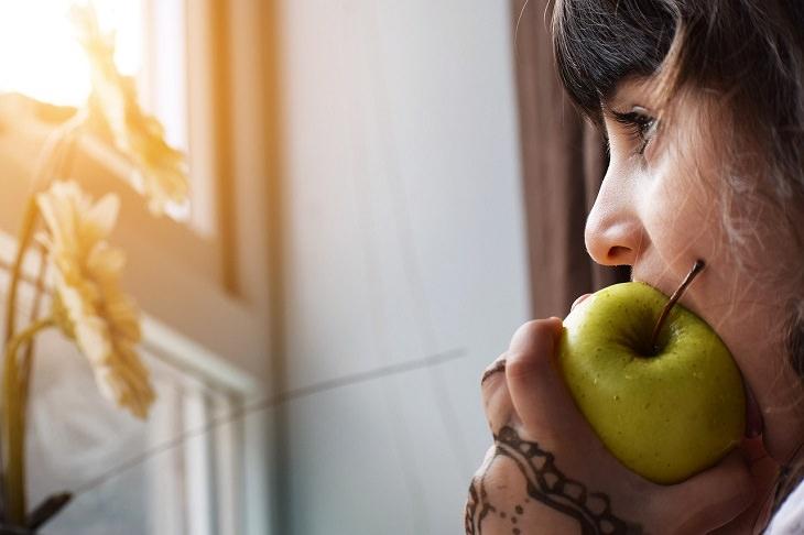 מחקר על תזונה ובריאות נפשית בקרב ילדים: ילדה אוכלת תפוח עץ