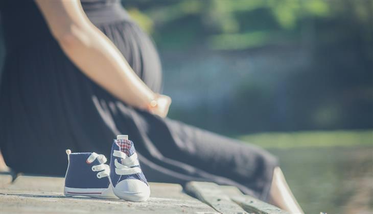 מחקר על פרצטמול והשפעתו על העובר: אישה בהריון יושב על רצפה ולידה נעלי תינוק