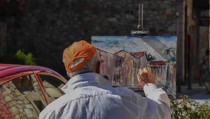 שלושת המפתחות של האושר: איש מבוגר מצייר על קנבס