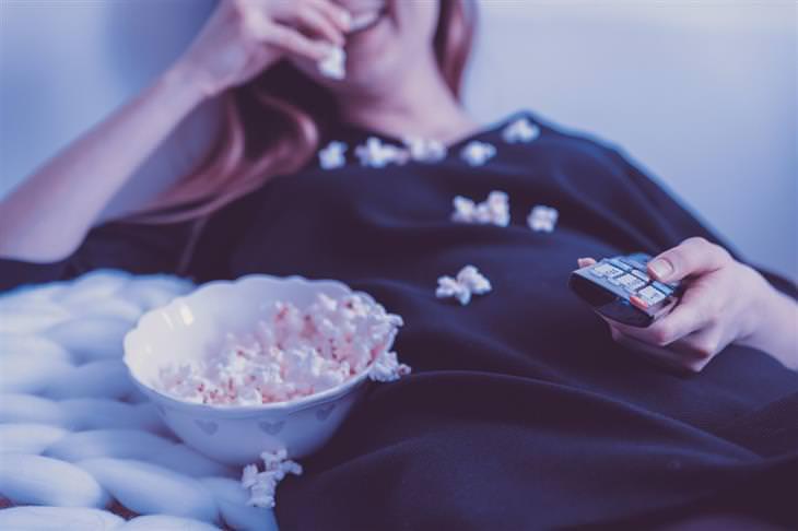 מנהגים יומיומיים שיכולים לשנות לכם את החיים: אישה צופה בטלוויזיה ואוכלת פופקורן