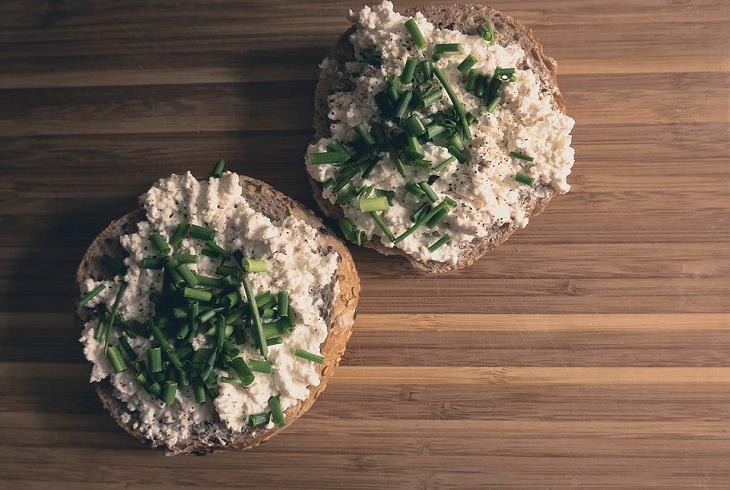 שימושים לחלב פג תוקף: שתי פרוסות לחם על שולחן מרוחות בגבינת קוטג'