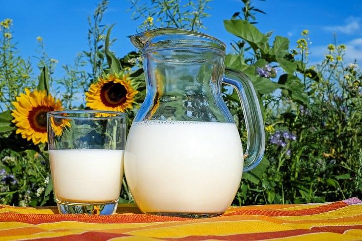שימושים לחלב פג תוקף: קנקן וכוס חלב על שולחן בחוץ, ברקע חמניות