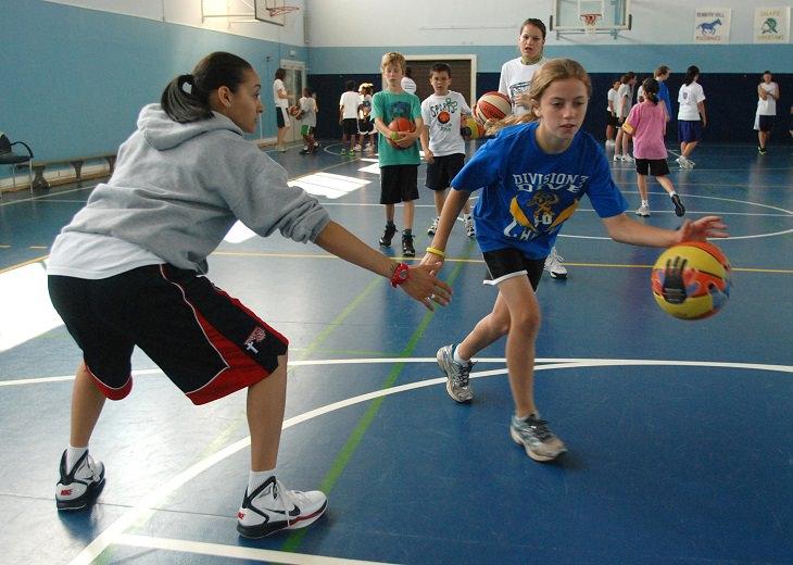 ספורט תחרותי: ילדה באימון כדורסל עוברת את המאמנת תוך כדי כדרור