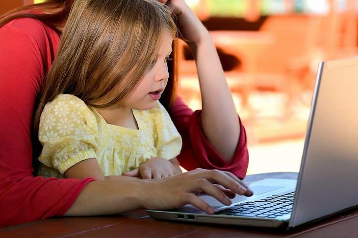 השפעה של הורות על הבריאות: ילדה יושבת עם אימא שלה מול מחשב נייד