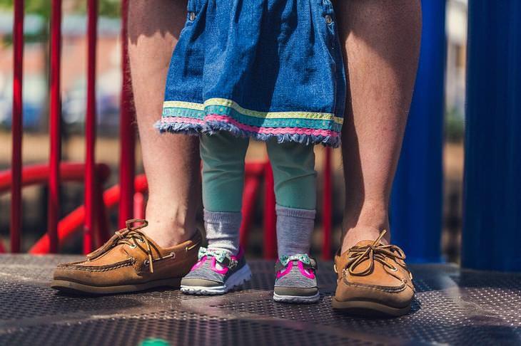 השפעה של הורות על הבריאות: רגלי גבר וילדה על מתקן שעשועים