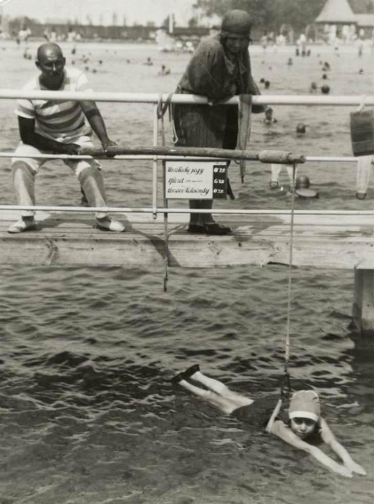 תמונות היסטוריות: ילדה קטנה מקבלת שיעורי שחיה בחופי צרפת, שנת 1908.