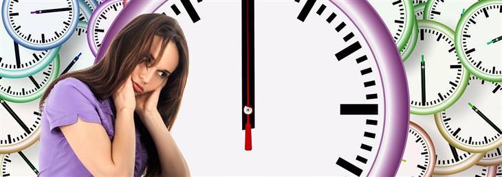 שיטות של פסיכולוגים להפגת מתח: אישה נראית מצוברחת על רקע שעונים