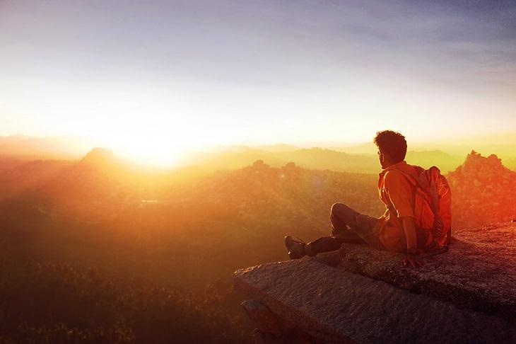 כללי בטיחות בטיולים: אדם יושב על קצה של הר בזמן הזריחה