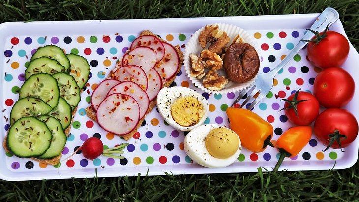 טיפים חלבון: מגש עם ירקות חתוכים, ביצה פרוסה ואגוזים