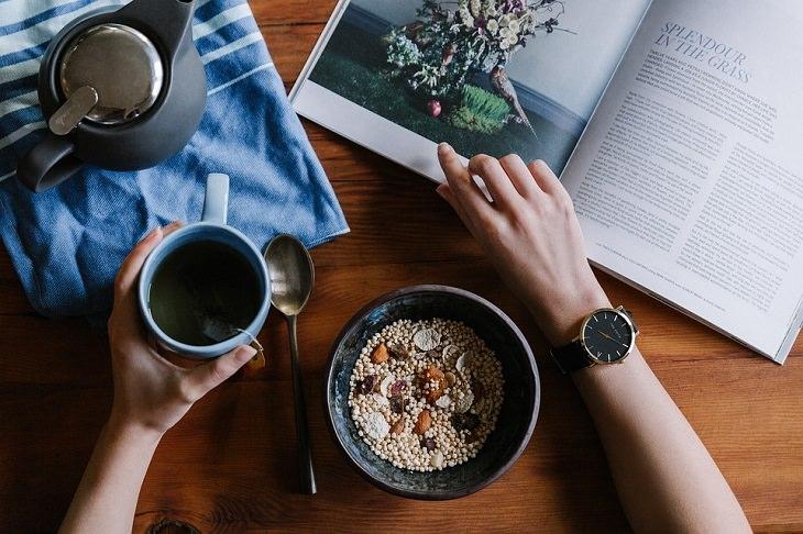 טיפים חלבון: מבט עילי על אדם אוכל קערת דגנים, שותה כוס תה וקורא עיתון