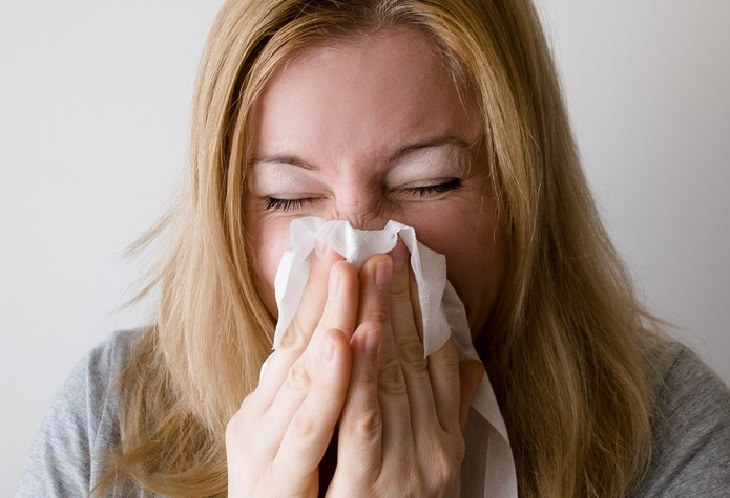 תופעות לוואי של הריון: אישה מקנחת את האף