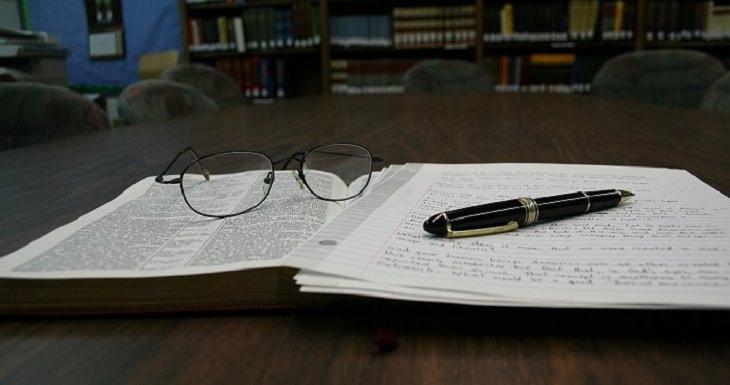 הפרעות קשב וריכוז: ספר קריאה עליו מונחים עט, משקפיים וחבילת דפי כתיבה